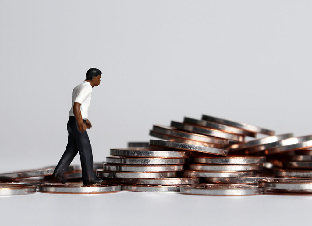 Image of black man represented by a toy figure standing in front of a pile of coins.