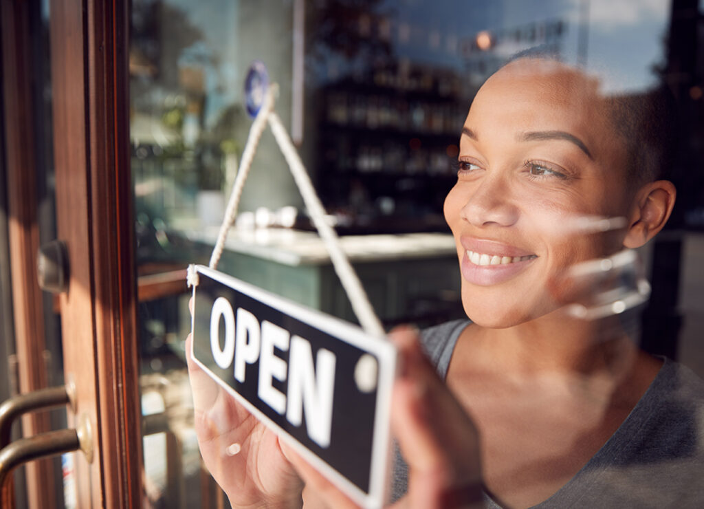 """Black, female business owner adjust """"open"""" sign in the window of her shop."""